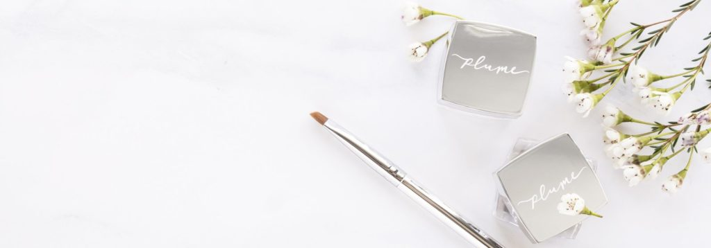 Plume Science Eyebrow Gel & Brush next to white flowers